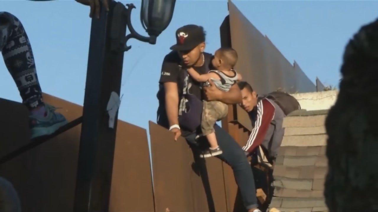Father, Baby Detained After Climbing Border Fence