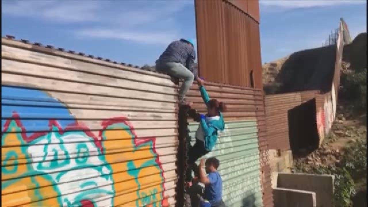 Watch: Migrants Climb Border Fence In Tijuana