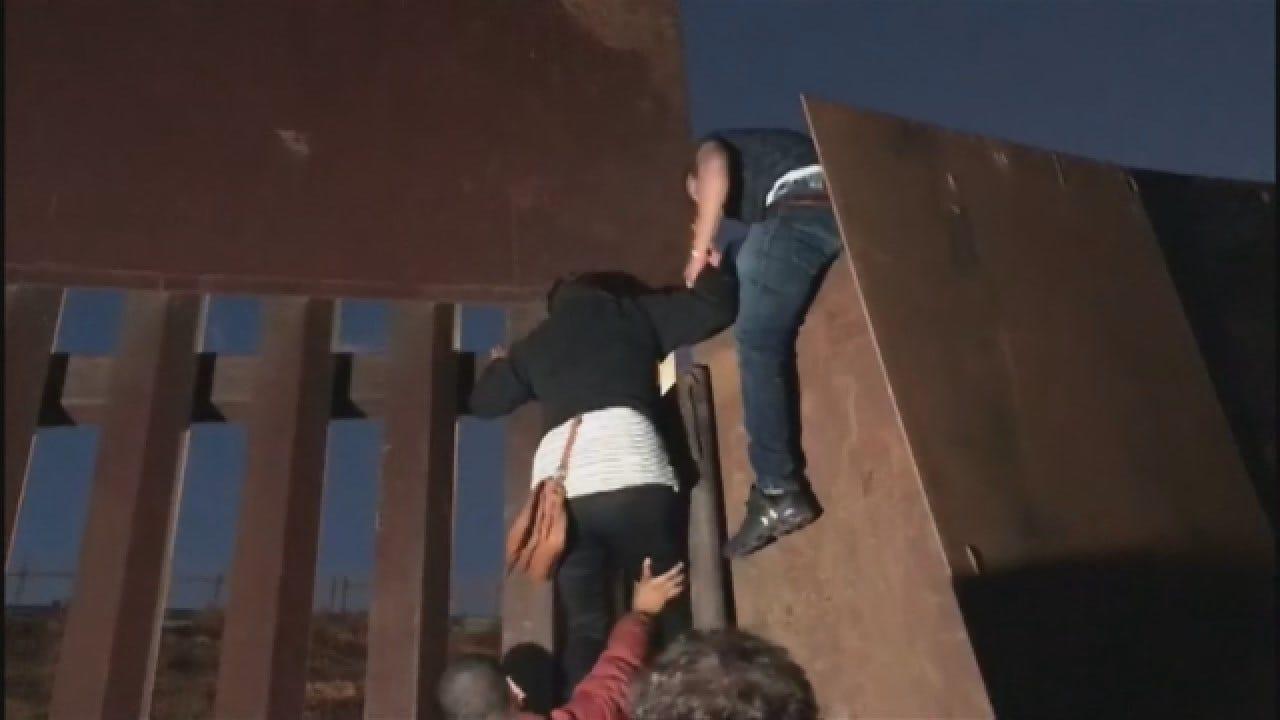 Migrants Jump Over Border Fence In Tijuana
